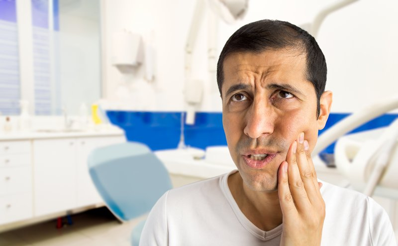 Man in dentist's office worriedly rubbing jaw
