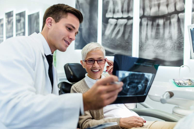 Periodontist teaching patient how to protect dental implants in Tallahassee.