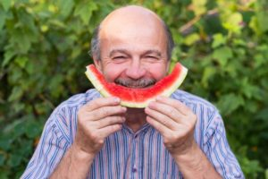 man eating summer foods with dental implants